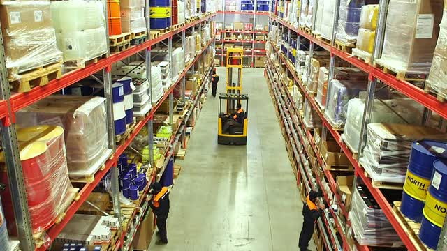 cardboard-boxes-inside-a-storage-warehouse-with-busy-workers-checking-stock-levels-and-using-a-forklift-truck-to-move-boxes_4ks1o4ec__M0000.jpg